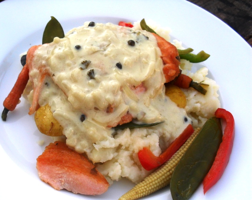 Salmon on mashed potatoes and stir fried vegetables with a green peppercorn sauce
