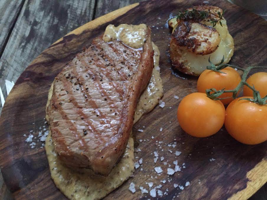 Sirloin steak with creamy mustard sauce and potato bake